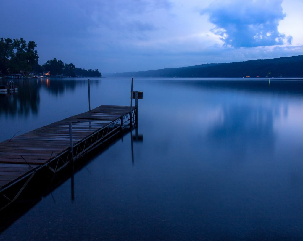 Storm coming over lake with dark blue sky during blue hour